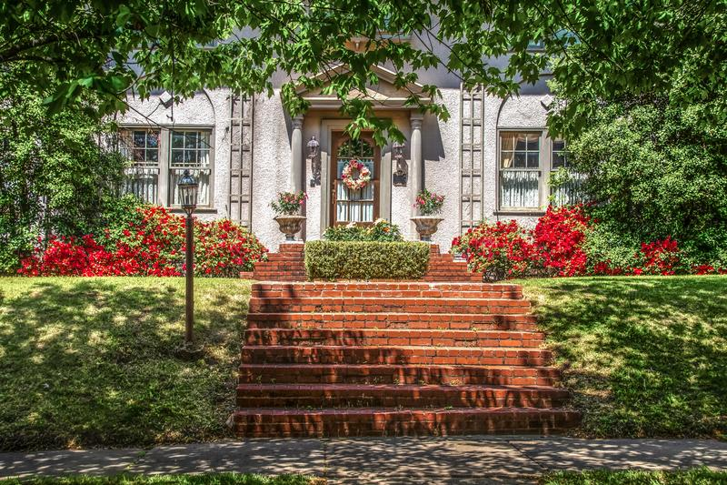 Acera dappled sombreada árbol y césped inclinado delante de la casa exclusiva del estuco con la guirnalda y las azaleas y los pas fotos de archivo libres de regalías