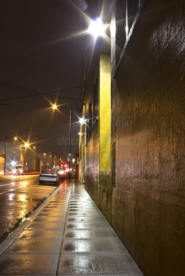 Acera y calle mojadas brillantes de la ciudad en la noche fotos de archivo libres de regalías