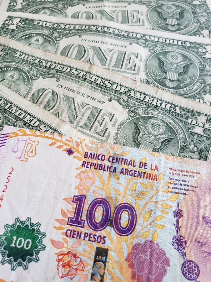 acercamiento al billete de banco de Argentina de 100 Pesos y billetes de dólar del americano uno foto de archivo