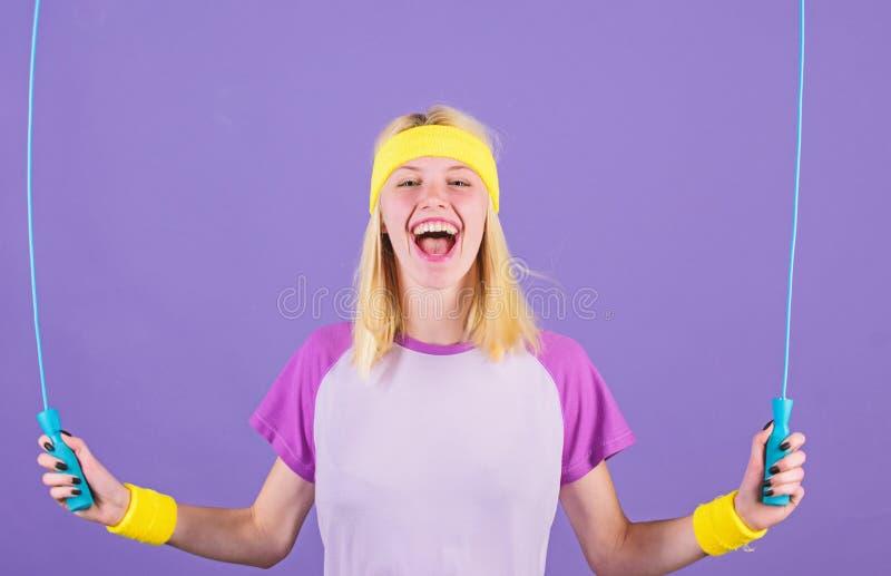 Acercamiento apropiado para perder el peso La cuerda de salto del control de la muchacha lleva pulseras brillantes Mujer que ejer fotos de archivo
