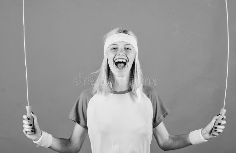 Acercamiento apropiado para perder el peso La cuerda de salto del control de la muchacha lleva pulseras brillantes Mujer que ejer fotos de archivo libres de regalías