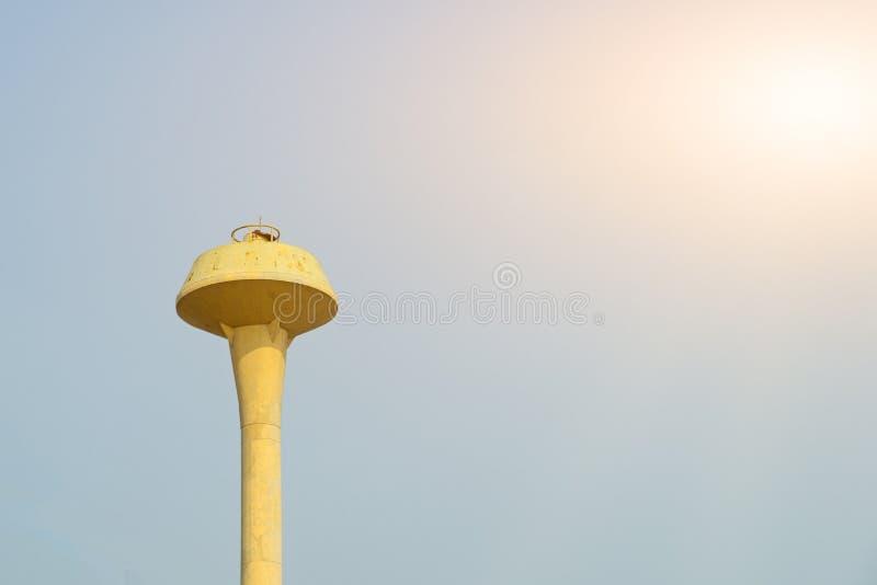 Acero amarillo del tanque del agua con el cielo azul fotografía de archivo