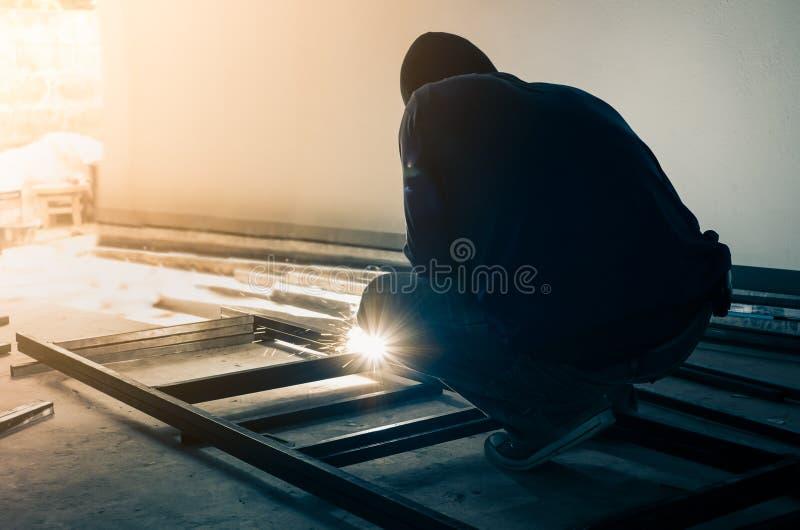 Acero de la soldadura del trabajador en sitio oscuro fotos de archivo