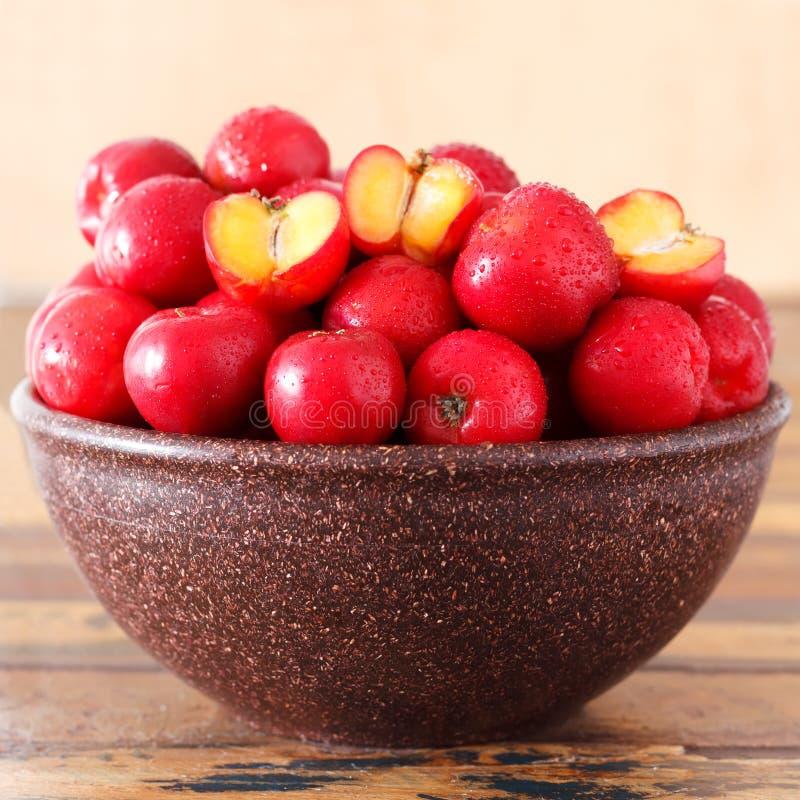 Acerola rouge (glabra de malpighie), fruit tropical dans la cuvette brune photographie stock libre de droits