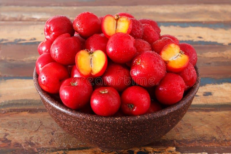 Acerola rouge - glabra de malpighie, fruit tropical dans la cuvette sur la table photo stock