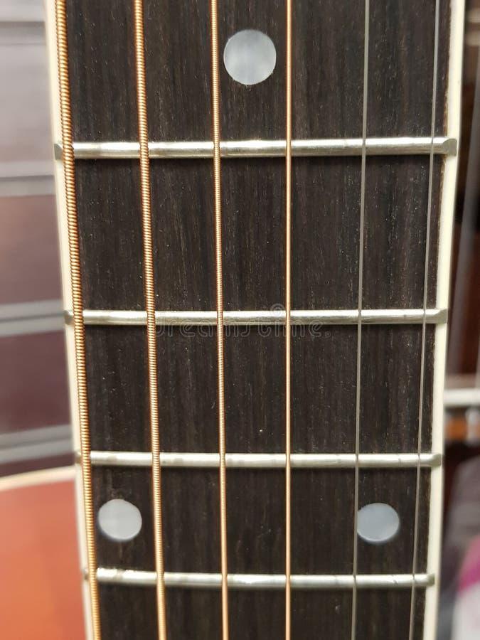 acerqúese al fingerboard de una guitarra acústica, de un instrumento musical, de un fondo y de una textura imágenes de archivo libres de regalías