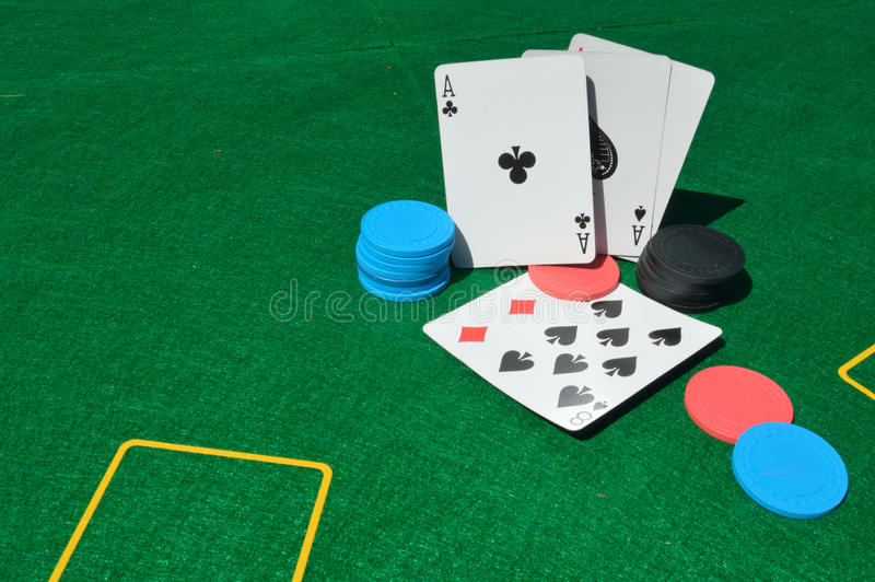Aces and eights. Poker chips and playing cards on green card table stock image