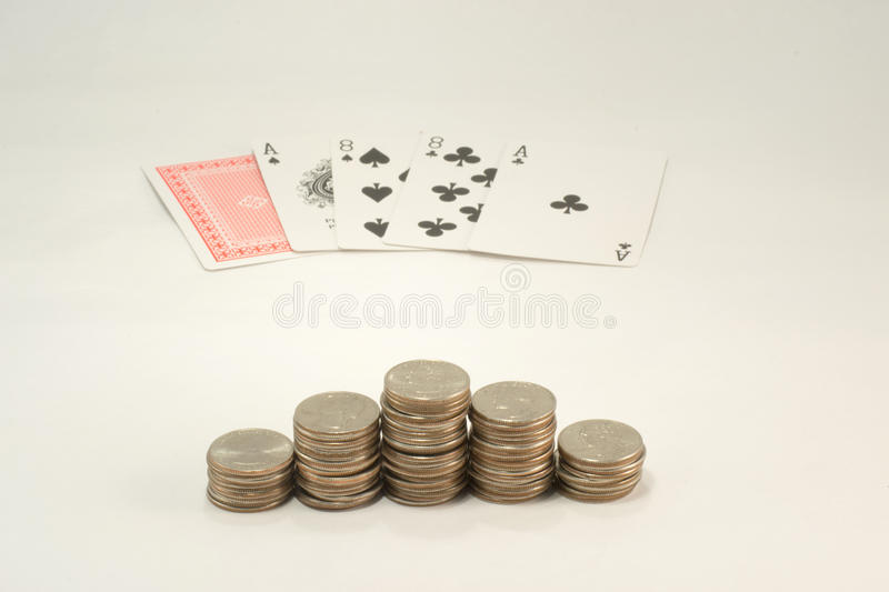 Aces and Eights and Pyramind of Quarters. Aces and eights (The Dead Mans Hand) and a pyramind of quarters on a light background stock photo