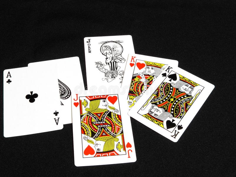 Aces, kings and a jack with a Joker at the back royalty free stock photo