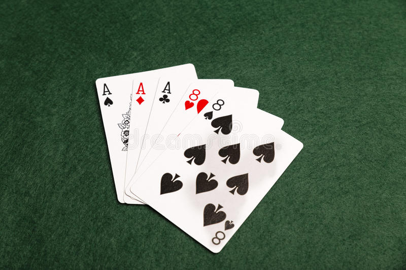 Aces Over Eights. A full house of three aces and two eights on a green baize background royalty free stock photography