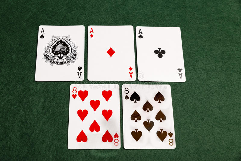 Aces Over Eights. A full house of three aces and two eights laid out on a green baize background royalty free stock images