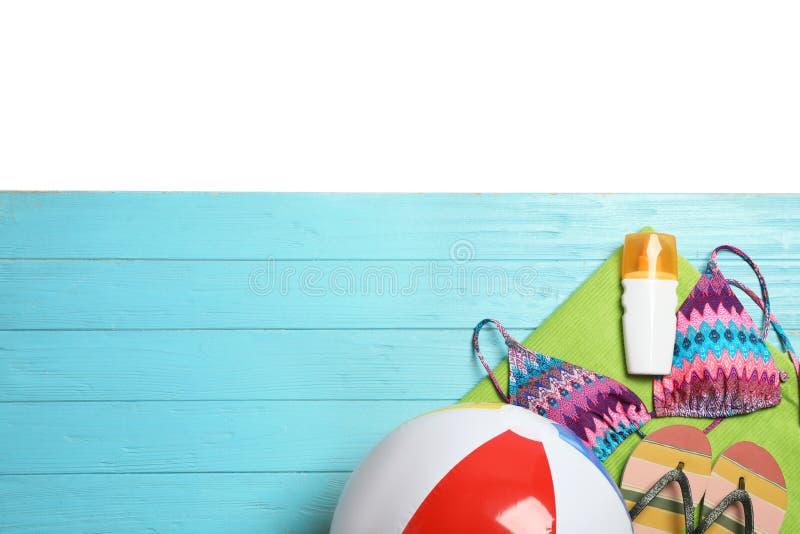Acessórios à moda diferentes da praia na tabela de madeira contra o fundo branco, vista superior fotografia de stock royalty free