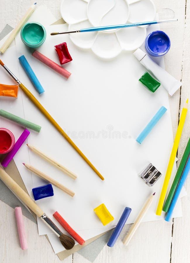 Acessórios à tiragem: papel, pinturas, escovas, lápis Vista superior foto de stock