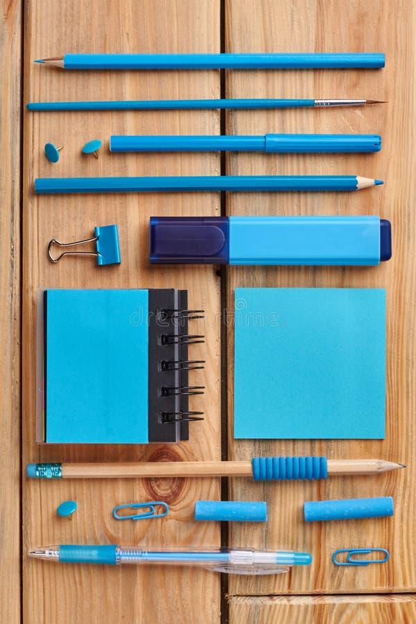 Acessórios azuis do escritório no fundo de madeira marrom imagens de stock