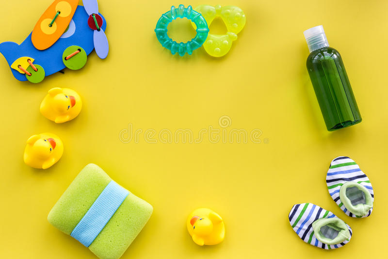 Acessórios, brinquedos e roupa do cuidado do bebê na zombaria amarela da opinião superior do fundo acima imagem de stock royalty free