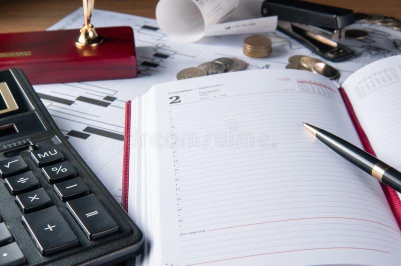 Acessórios caderno do negócio, calculadora, pena de fonte e gráficos, tabelas, cartas em uma mesa de escritório de madeira imagens de stock