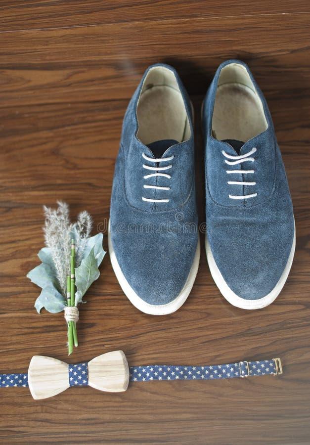 Acessórios clássicos do noivo: laço de madeira e sapatas azuis em uma tabela de madeira fotografia de stock