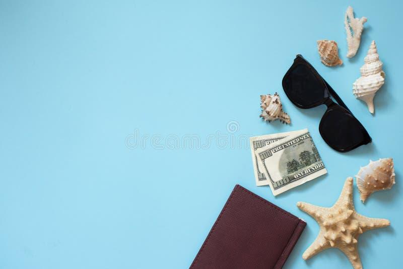 Acessórios colocados lisos do viajante no fundo azul com escudos, dinheiro, bloco de notas e óculos de sol do mar r imagem de stock