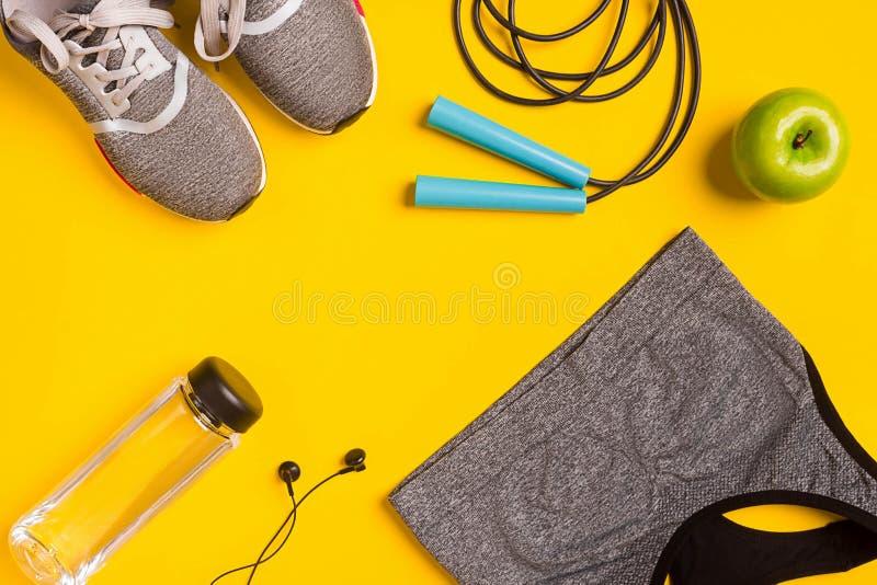 Acessórios da aptidão no fundo amarelo As sapatilhas, a garrafa da água, os fones de ouvido e o esporte cobrem fotos de stock royalty free