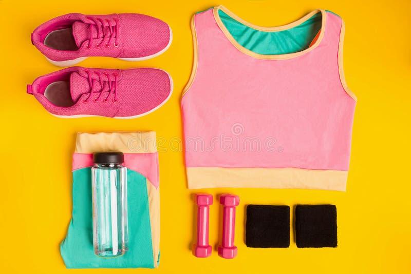 Acessórios da aptidão no fundo amarelo As sapatilhas, a garrafa da água, os pesos e o esporte cobrem fotografia de stock royalty free