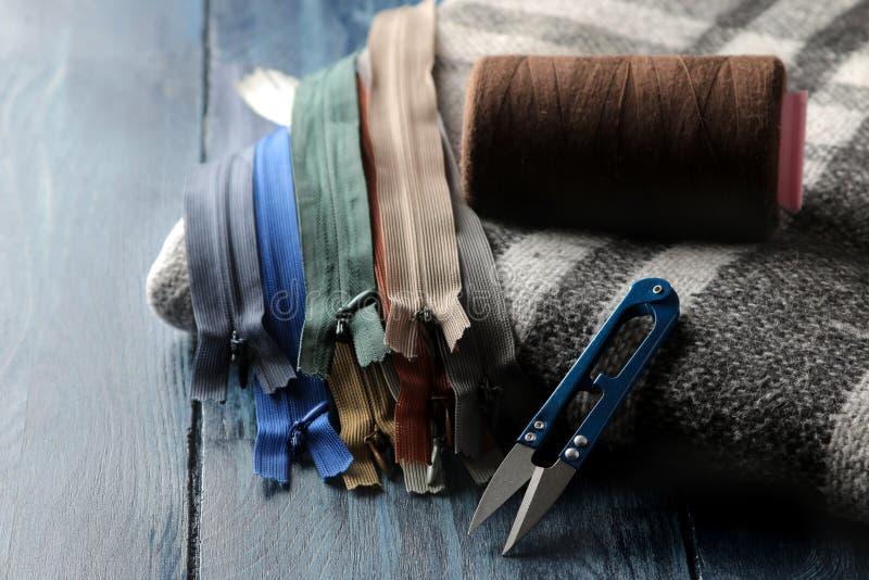 Acessórios da costura e do bordado, tesouras em um fundo de madeira azul imagem de stock royalty free