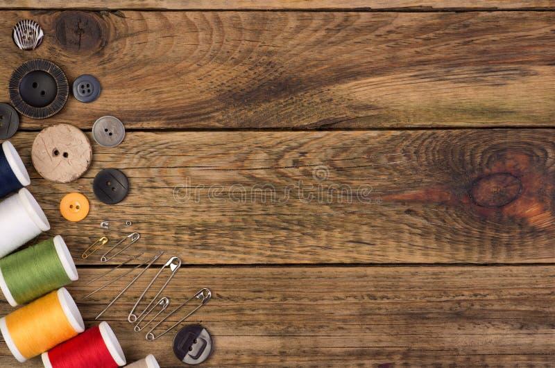 Acessórios da costura no fundo de madeira foto de stock