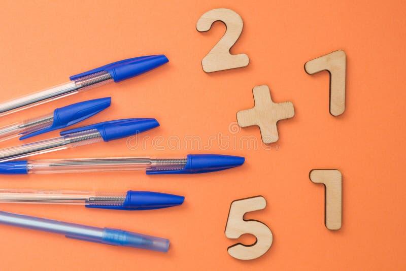 Acessórios da escola, penas azuis em um fundo alaranjado Números matemáticos para crianças imagens de stock royalty free