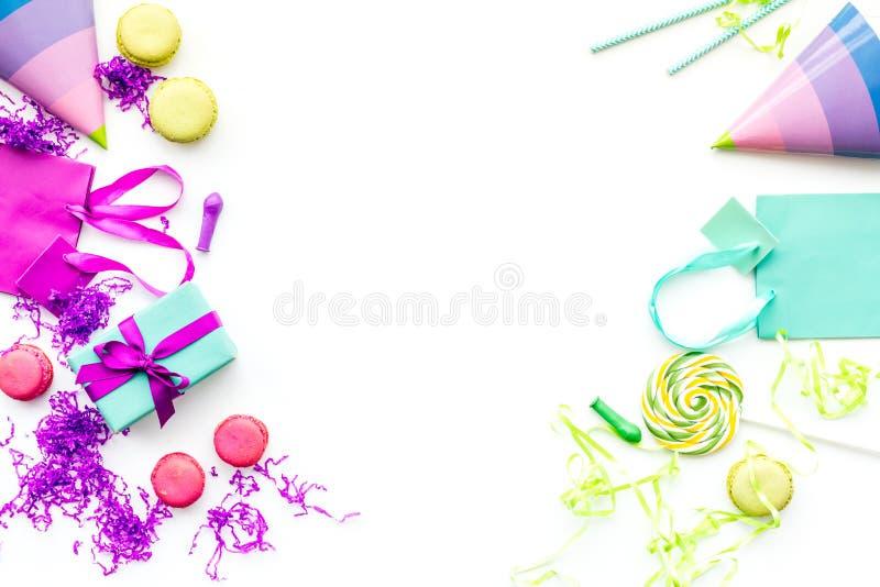 Acessórios da festa de anos Caixa de presente, saco de papel, chapéu do partido, doces, confetes no espaço branco da cópia da opi fotografia de stock royalty free