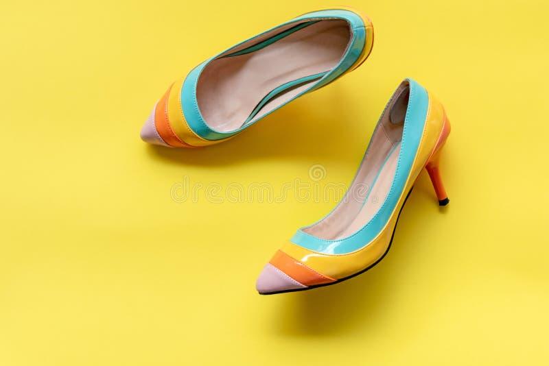 Acessórios da mulher da forma ajustados Saltos coloridos das sapatas da forma na moda Fundo amarelo da cor pastel, vista superior fotos de stock royalty free