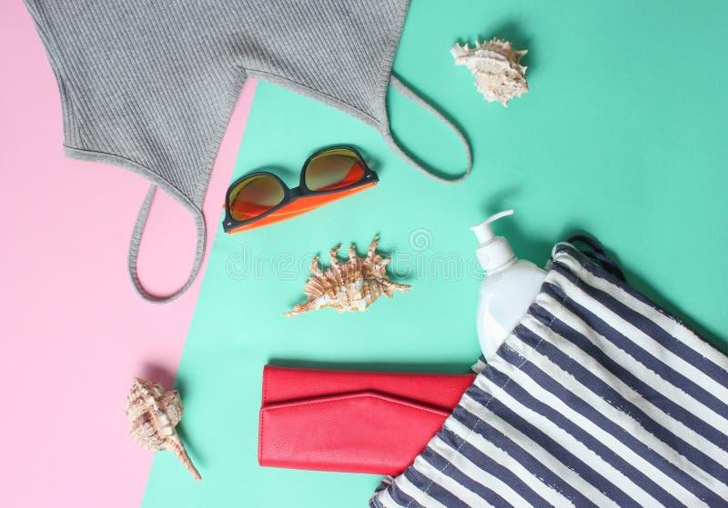 Acessórios da praia em um fundo pastel colorido Saco da praia, t-shirt, óculos de sol, bolsa, sunblock, cockleshells Vista superi imagem de stock