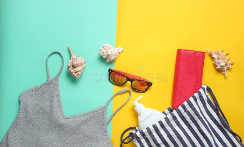 Acessórios da praia em um fundo pastel colorido Saco da praia, t-shirt, óculos de sol, bolsa, sunblock, cockleshells Vista superi fotos de stock royalty free