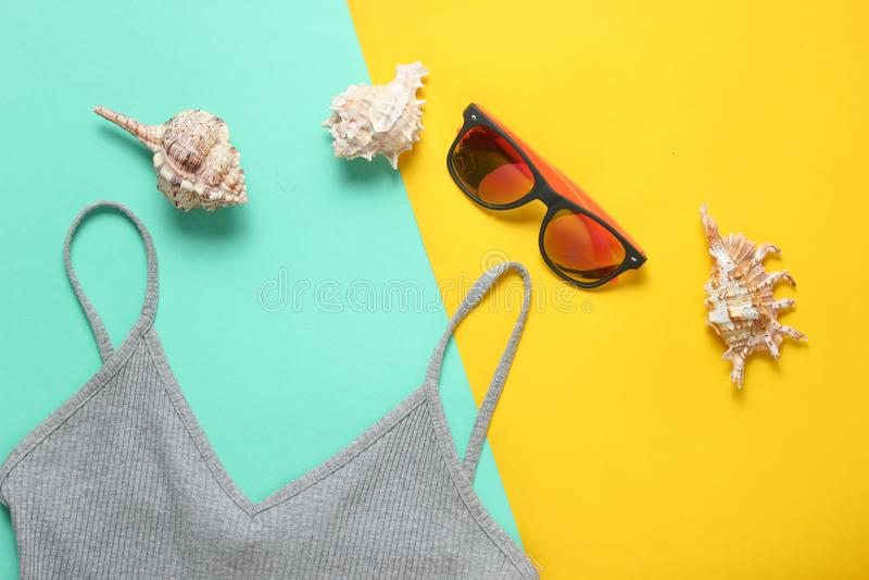 Acessórios da praia em um fundo pastel colorido T-shirt, óculos de sol, sunblock, cockleshells Vista superior foto de stock
