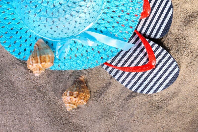 Acessórios da praia Flip-flops, um chapéu e conchas do mar na areia do mar imagem de stock