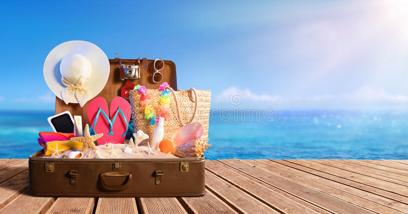 Acessórios da praia na mala de viagem na praia foto de stock royalty free