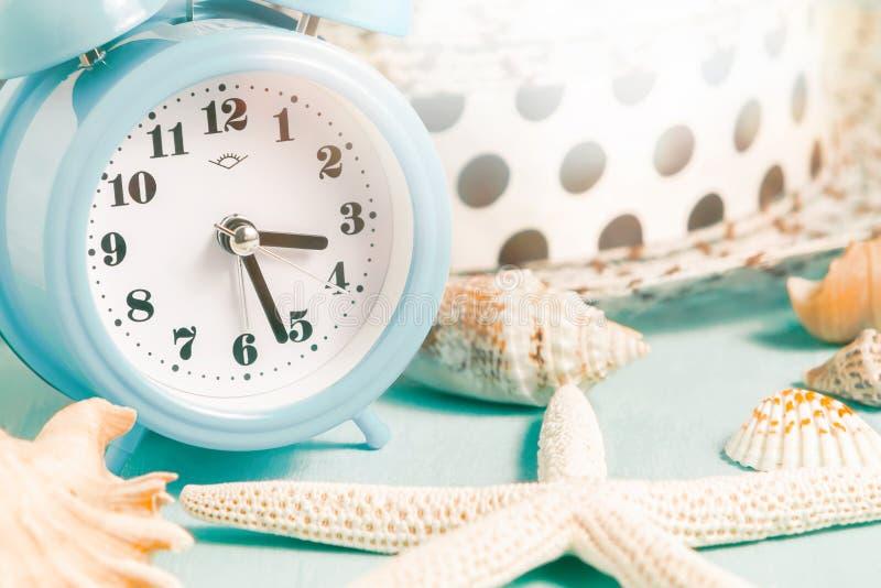 Acessórios das conchas do mar, do despertador e da praia em uma tabela azul - conceito das férias de verão e do tempo de férias imagens de stock royalty free