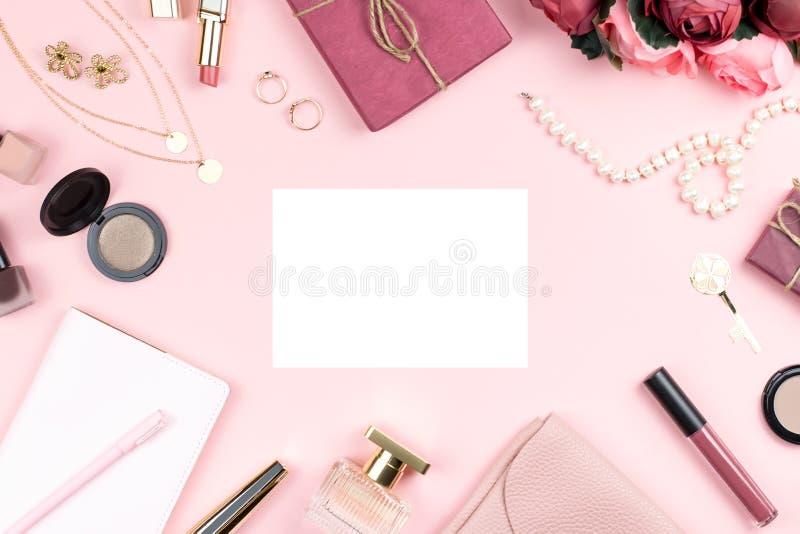 Acessórios de forma da mulher, flores, cosméticos e joia no fundo cor-de-rosa, copyspace Conceito do dia das mulheres fotografia de stock