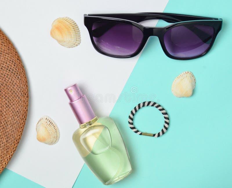 Acessórios de forma fêmeas em um fundo pastel branco azul Óculos de sol, garrafa de perfume, cockleshells, chapéu Praia do verão foto de stock royalty free