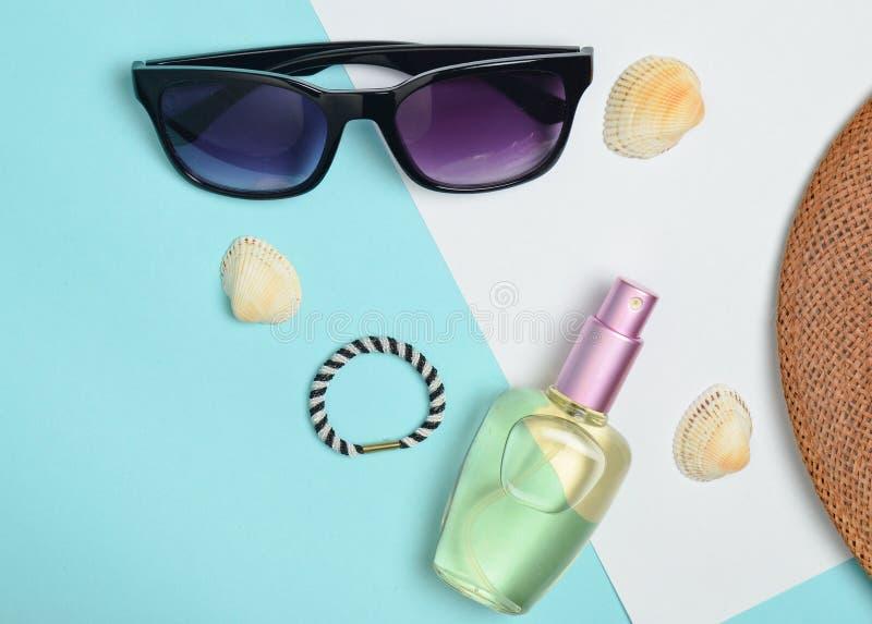Acessórios de forma fêmeas em um fundo pastel branco azul Óculos de sol, garrafa de perfume, cockleshells, chapéu Praia do verão imagens de stock royalty free