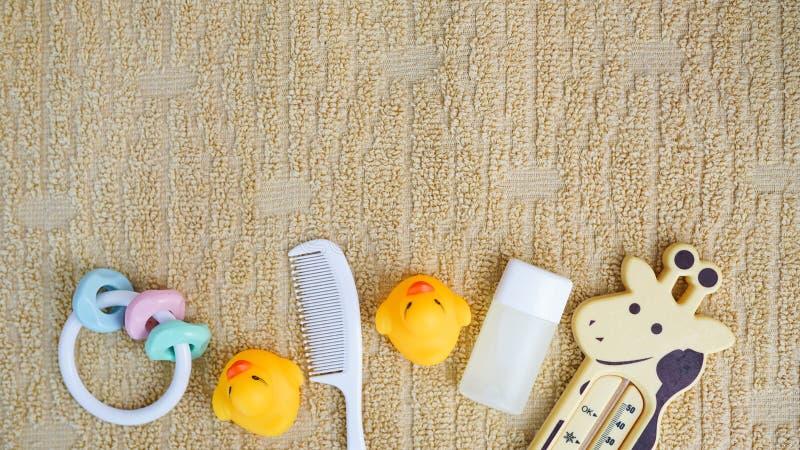 Acessórios do bebê para banhar-se e brinquedo na toalha com espaço da cópia, configuração lisa foto de stock royalty free