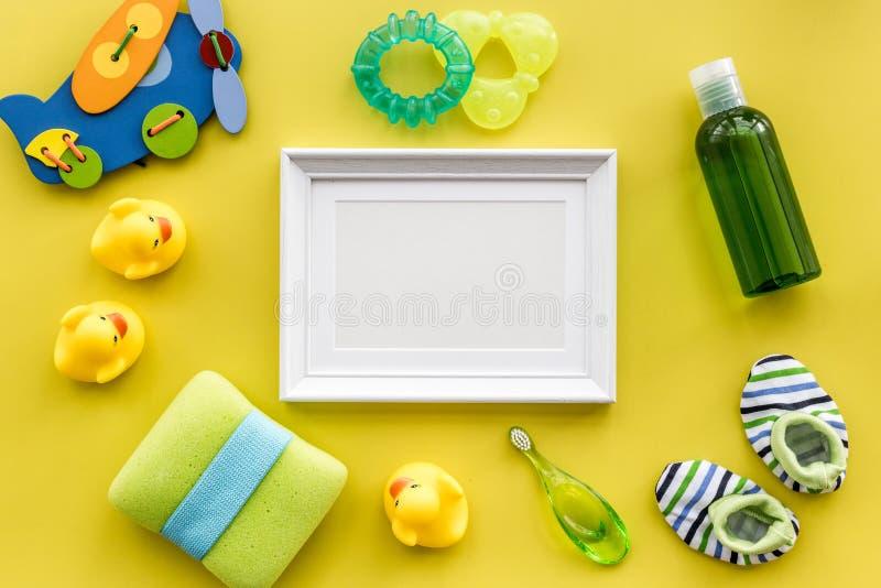 Acessórios do bebê para o banho com cosmético, quadro e patos do corpo no modelo amarelo da opinião superior do fundo imagens de stock royalty free