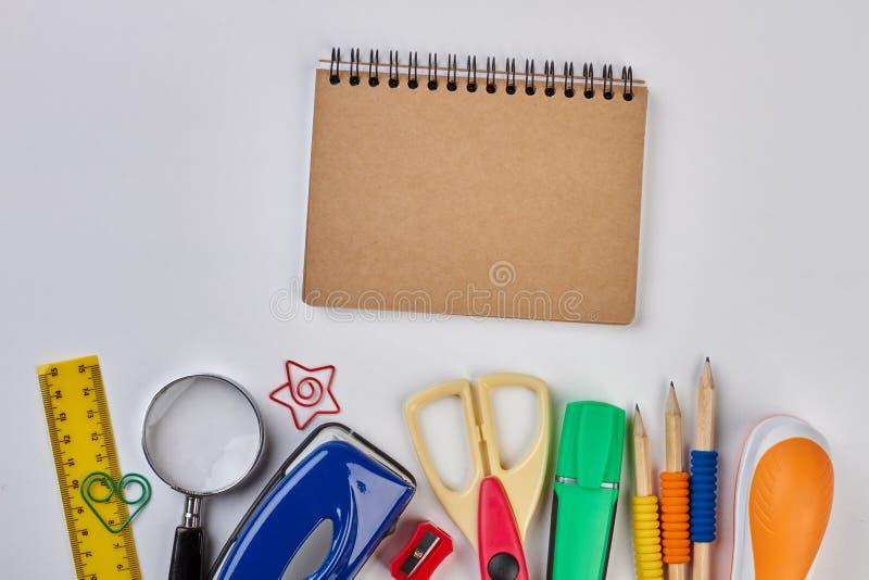 Acessórios do caderno e da escola no fundo branco imagens de stock