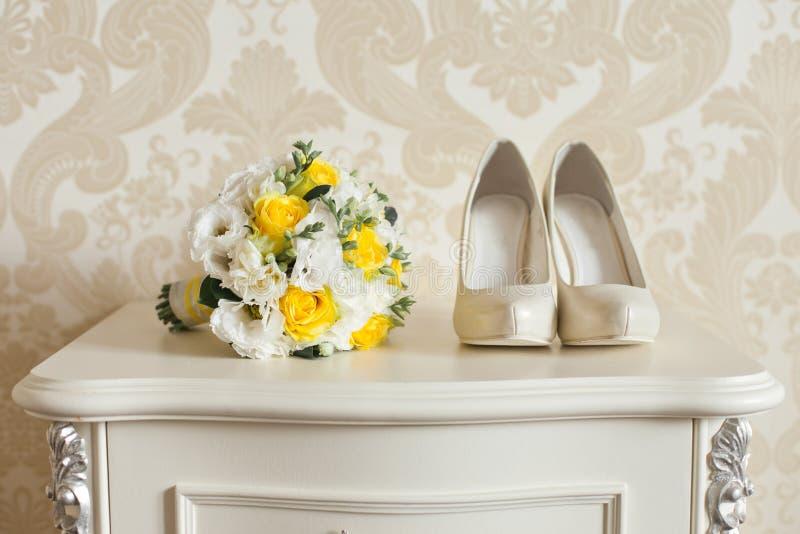 Acessórios do casamento do ` s da noiva: sapatas do casamento e ramalhete ou boutonniere fotografia de stock
