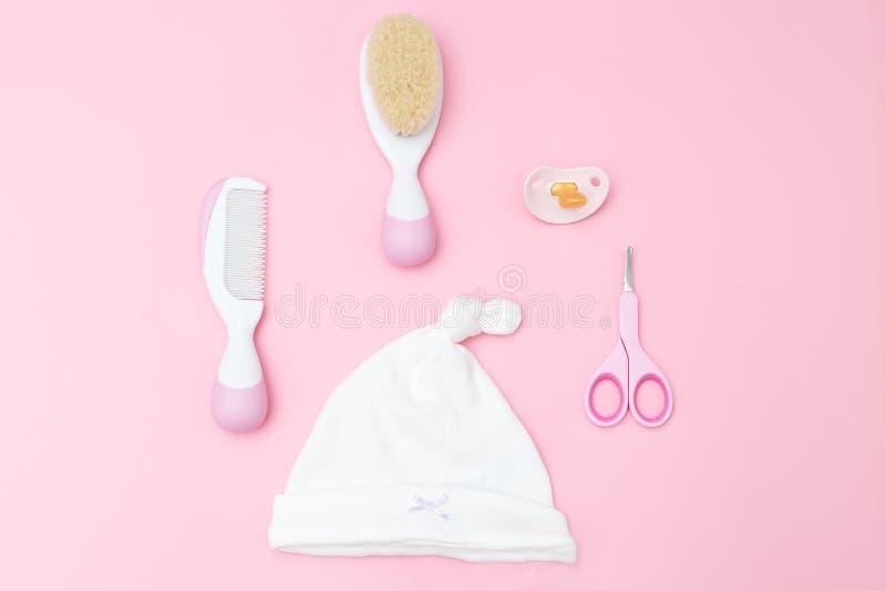 Acessórios do cuidado do bebê no fundo cor-de-rosa Configuração lisa foto de stock