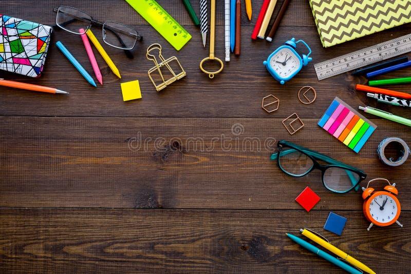 Acessórios do estudante Quadro com vidros, despertador dos artigos de papelaria, caderno no espaço de madeira escuro da opinião s imagem de stock