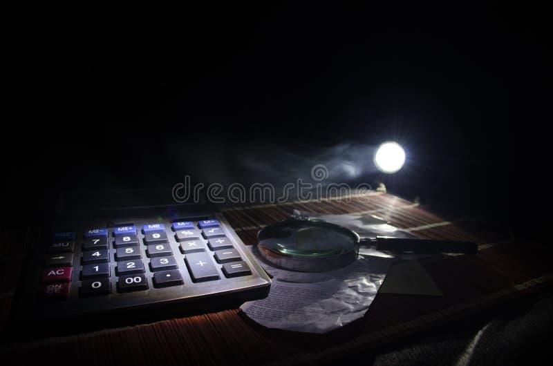 Acessórios do negócio (lente de aumento, calculadora) e gráficos, tabelas, cartas em uma tabela com fundo escuro Foco seletivo fotografia de stock