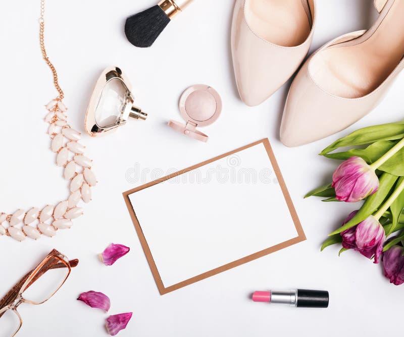 Acessórios do ` s da mulher da cor bege, de tulipas cor-de-rosa e do papel vazio fotos de stock royalty free