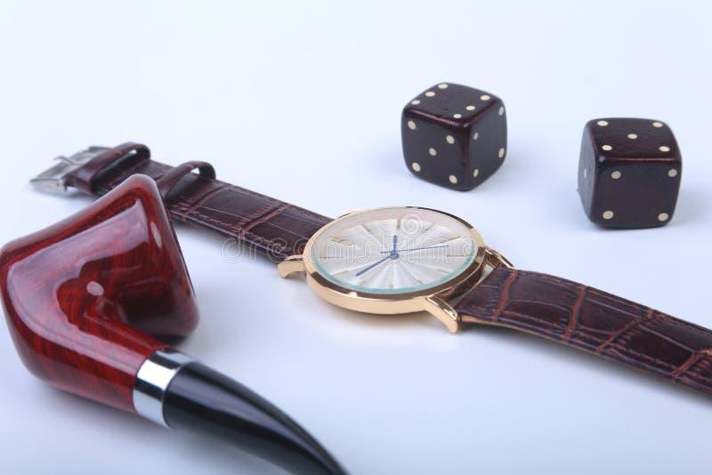 Acessórios do ` s dos homens para o negócio e o rekreation Relógio, tubulação de fumo e dados no fundo branco Composição da vista fotografia de stock royalty free
