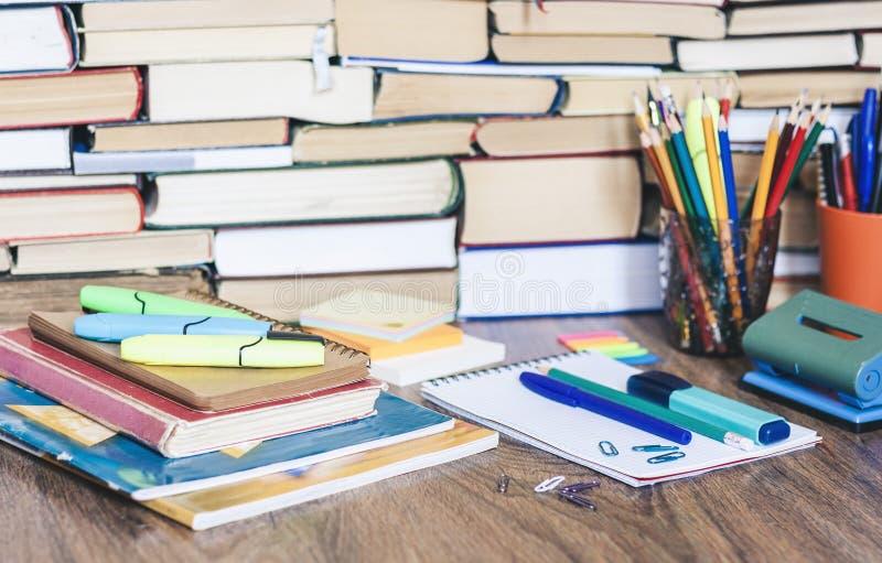 Acessórios dos artigos de papelaria da escola - caderno, pilha do caderno com os lápis plásticos do suporte, penas, marcadores, c foto de stock