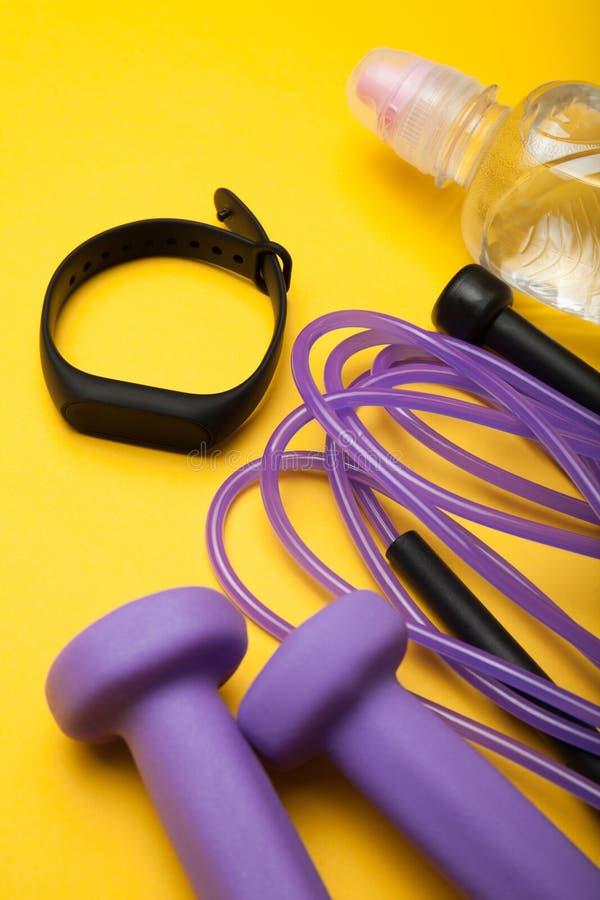 Acessórios dos esportes - corda de salto, pesos, bracelete da aptidão e água Fundo amarelo fotos de stock royalty free