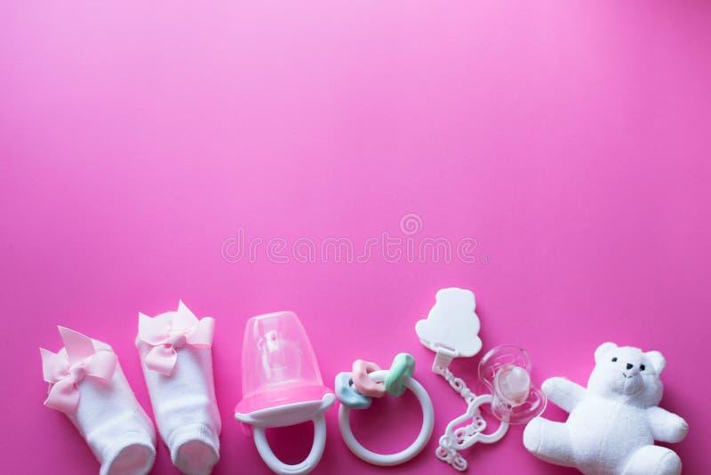 Acessórios e brinquedos do bebê no fundo cor-de-rosa o plano da criança coloca com brinquedos brancos fotos de stock royalty free